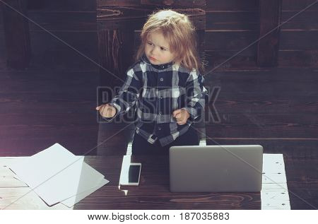cute boy kid in office with laptop phone and paper sheet
