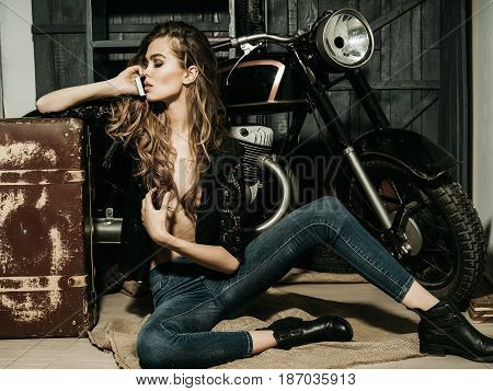 girl biker or pretty woman with long blond hair in erotic shirt and jeans with vintage suitcase at bike in garage with mobile phone on grey wooden background.