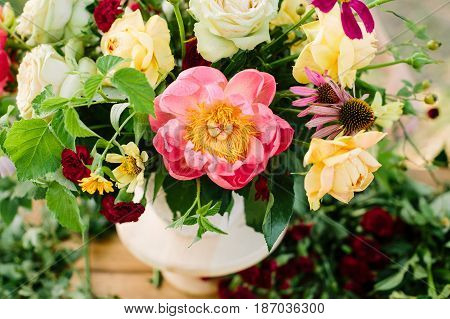 floral design, decoration, applied art, wedding, spring concept - flower bouquet arranged of blooming english roses and avalanches, coral peonies and diathuses, decorated with raspberry leaves