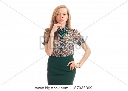 beautiful young girl with blond hair and attire keeps one hand near the face and the other on the side and looks straight isolated on white background.