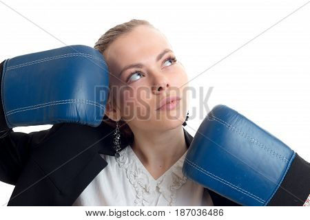 Portrait of a charming blonde that looks up and keeps hands near the person in blue boxing gloves isolated on white background
