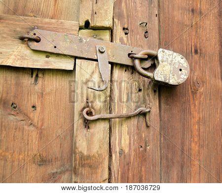 The old lock and hook lock a wooden door. Rural ancient design.
