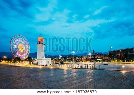 Batumi, Adjara, Georgia - May 26, 2016: Ferris Wheel In Motion And Pitsunda Lighthouse At Promenade In Miracle Park, Amusement City Park On Blue Evening Sky And Hilly Background. Blue Hour. Evening Or Night Time