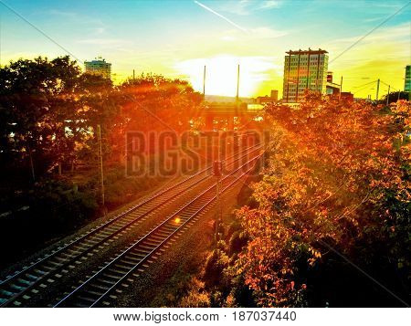 Photo of a sunset with houses trees an train tracks