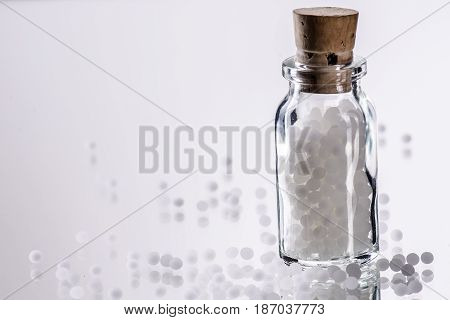 white homepathic globules in a small bottle of glas - selected focus; narrow depth of field