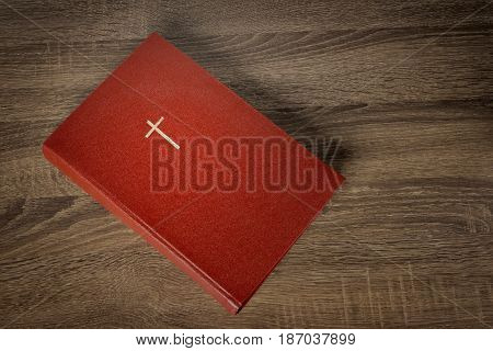 Red bible with cross on cover, wooden table background