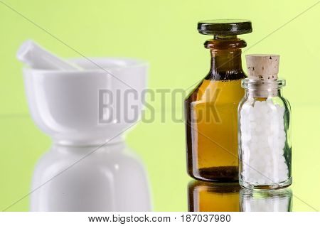 homeopathic pills with glassbottle and mortar green background