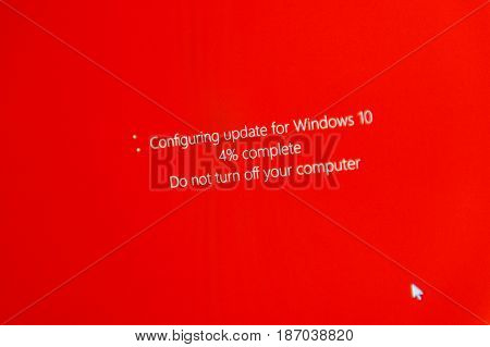PARIS FRANCE - JAN 7 2016: Configuring update for microsoft Windows 10 operating system OS with percentage bar and message to not turn off the computer - message on red background