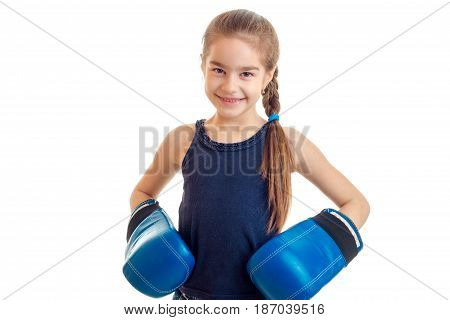 beautiful little girl smiling looking directly and keeps hands in boxing gloves is isolated on a white background close-up
