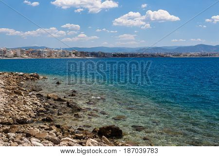 Coast landscape with stony beach, city and blue sea.