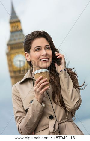 Girl or young woman with perfect teeth drinking coffee in a disposable cup and using a mobile cell phone with Big Ben in the background, London, England, Great Britain
