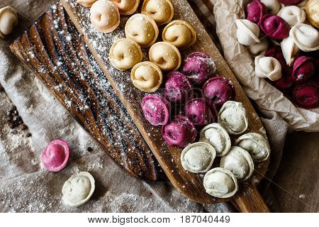 Fresh pink yellow beet dumplings or ravioli stuffed with ricotta cheese with butter sauce on wooden board on dark background.