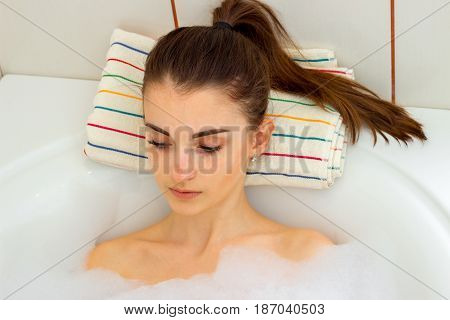 Portrait of a charming girl with a ponytail that rests in a hot tub with foam close-up