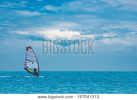 Alone surfer on board in sea with beautiful clouds in a sky