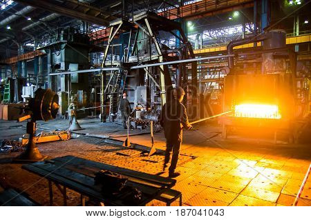 Heavy forgings Plant. workers carry a workpiece from the furnace to the hammer
