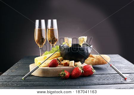 Gourmet Swiss Fondue Dinner With Assorted Cheeses On A Board And Strawberries Alongside A Heated Pot