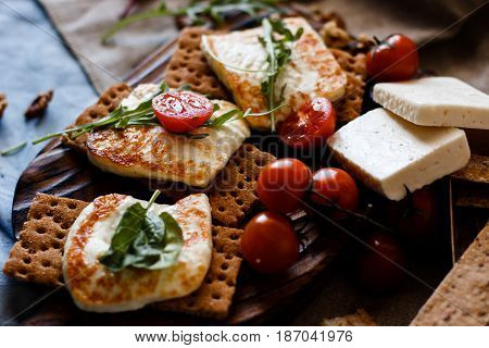 Grilled homemade halloumi cheese with fresh green herbs over wooden background, top view, close-up.