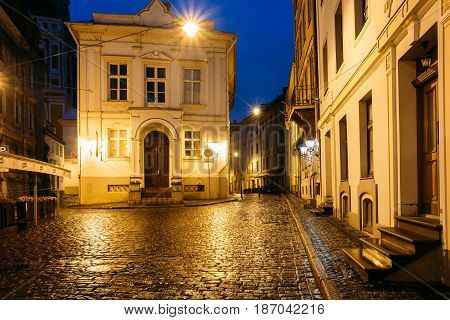 Riga, Latvia - July 3, 2016: Old Building At Intersection Of Maza Pils And Klostera Streets In Evening Or Night Illuminations Lights In Old Town