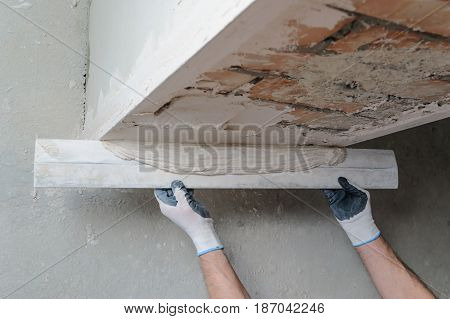 Worker's hands are using a ruler for gypsum plaster.