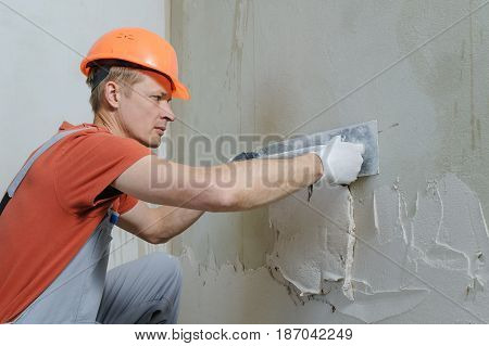 Worker is putting a gypsum plaster on a wall. He is using a long trowel.