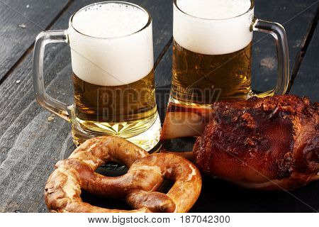 Baked Pork Shank And Honey Sause And Glass Of Beer On A Dark Wooden Table.