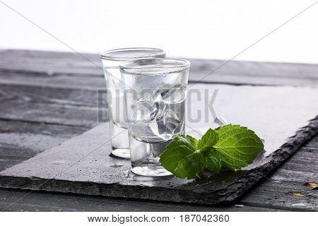 Vodka in shot glasses on black stone background