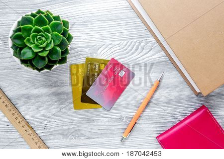dollar sign and credit cards for fee-paying education on gray wooden student desk background top view mockup