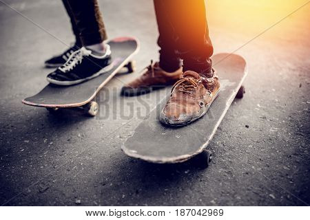 Boys skateboarders Feet in pants and bryaks in frayed sneakers stand on the skateboard. Concept of a team of friends doing sports on the asphalt skateboarding Go ahead and lead the youth.