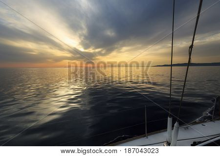 Fantastic sunset over a calm sea seen from sailboat. Dramatic reflection of clouds