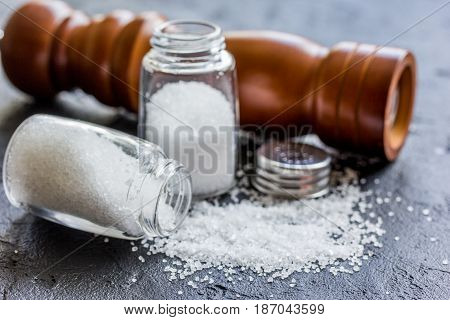 salt in glass bottle with saltcellar on black stone kitchen table background