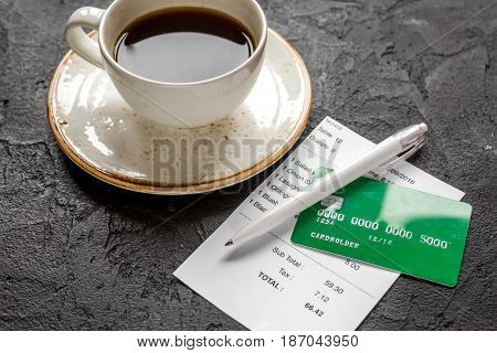 cup of coffee and receipt bill for payment by credit card on dark table background