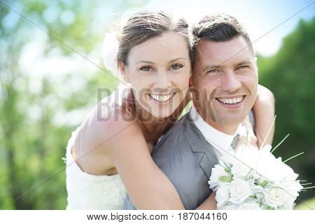 Groom giving piggyback ride to bride in countryside