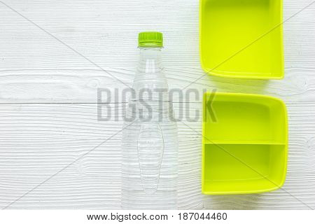 homemade lunch with green lunchbox and water on wooden table background top view mockup