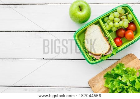 homemade lunch with apple, grape and sandwich in green lunchbox on white wooden table background top view mockup