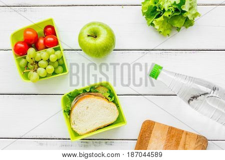 healthy break with apple, grape and sandwich in green lunchbox on home wooden table background flat lay