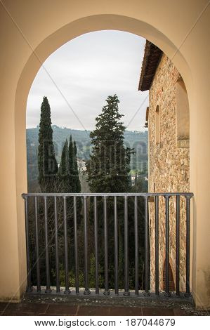 View of trees and building wall from an arch. Florence. Italy. Vignette effect.