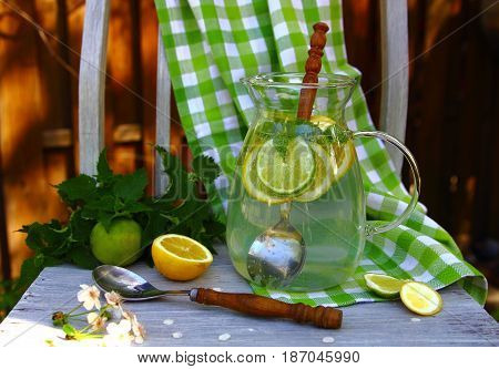 carbonated lemonade in the pitcher on the chair in the garden with a wooden spoon
