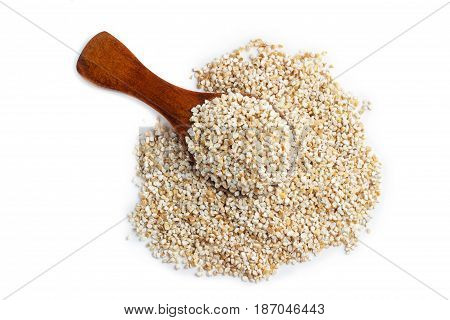 Barley groats on wooden spoon isolated on white background. Top view.
