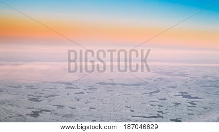 Panoramic Aerial View From High Altitude Flight Of Aircraft On Snow-covered Ground In Winter At Sunset Sunrise. Forests And Fields. Clear Sunny Dawn Sky With Cold And Warm Colors.
