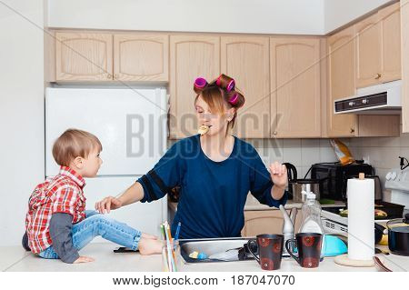 Busy white Caucasian young woman mother housewife with hair-curlers in her hair cooking preparing dinner meal in kitchen child son boy sitting on table crazy parent life