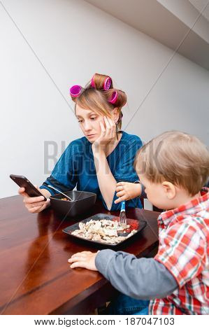 Bored tired white Caucasian young woman mother housewife with hair-curlers in hair looking on phone surfing Internet f child son boy sitting eating meal lunch lifestyle concept
