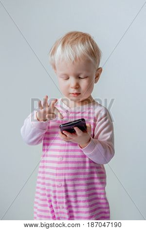 Cute adorable white Caucasian blond baby with blue eyes making a call playing with mobile cell phone with funny expression on her face lifestyle new generation technology