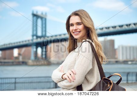 Beautiful smiling student girl traveling with backpack in New York City