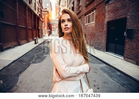 Beautiful lonely girl walking on epmty city strret looking up to the side. City urban people lifestyle concept.