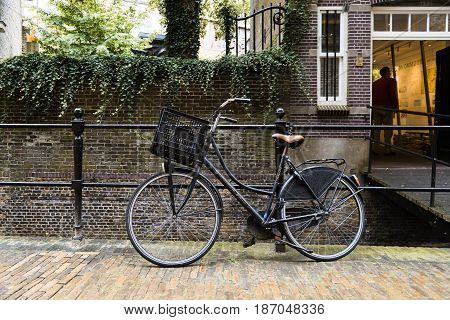 Gouda Netherlands - August 4 2016: Bicycle parked by the canal in a picturesque street in the dutch city of Gouda