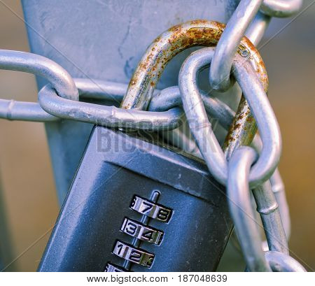 Stock image of a weathered combination lock on a chain