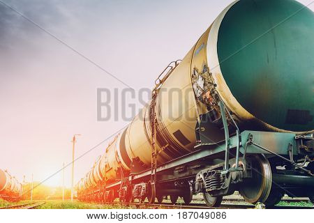 Tanks with gas or oil transportation by railroad at sunset, copy space