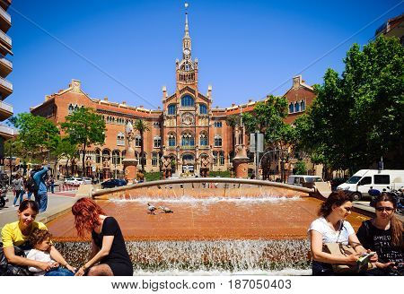 BARCELONA, SPAIN - MAY 2017: People are sitting near small fountain near Building of Old Hospital de Sant Paul in Barcelona, Spain