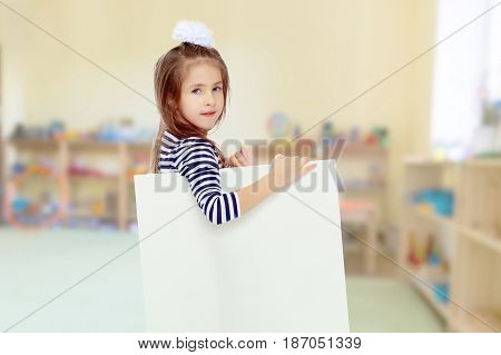 The little blonde girl with long hair and with a white bow on her head , in a blue striped summer dress.She peeks out from behind white banner.In the Montessori room.