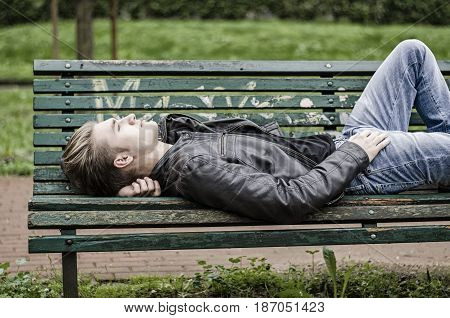 Handsome blond young man laying on green, wooden park bench. thinking